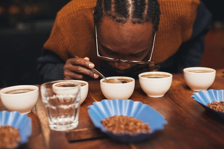 Croped shot of an African man bending down to smell the aroma of a cup of fresh coffee, that is part of a row of a variety of coffees on a wooden counter with roasted coffee beans