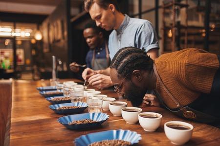 tostadora moderna con tres baristas entrenamiento con una variedad de granos de café tostado y molido recién hecho en un mostrador de madera