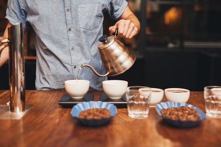 Professional barista pouring hot water into a cup of freshly ground coffee with open containers of coffee beans on a wooden counter in a roastery
