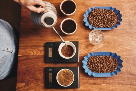 Overhead shot of a professional barista pouring hot water from a stainless steel kettle into a cup with ground coffee, testing for a perfect cup while it is resting on digital scale on a wooden table