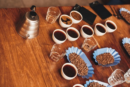 High angle view of a wooden table with many cups of coffee, fresh roasted beans in open continers, water glasses, a stainless steel kettle and digital scales ready for a coffee tasting
