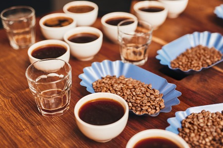 Many cups of coffee with open containers of freshly roasted coffee beans in a variety of flavours, and some water glasses on a wooden table for a tasting