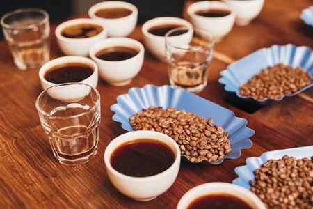 Viele Tassen Kaffee mit offenen Behältern von frisch gerösteten Kaffeebohnen in einer Vielzahl von Aromen und einige Wassergläser auf einem Holztisch für eine Verkostung