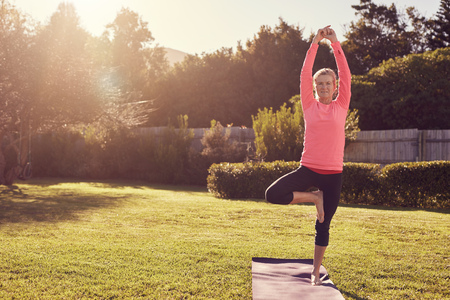 Athletic senior woman standing confidently in a balancing pose on her yoga mat, in her garden on the grass, with morning summer sunflare filtering through the trees