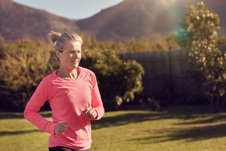 sportsperson: Athletic senior woman in a pink sportswear top, training by doing some jogging outdoors with grass and trees, on a sunlit morning Stock Photo