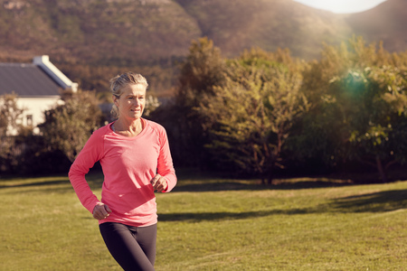 jog: Senior woman in atheltic wear enjoying a morning jog outdoors, with grass and trees around her and gentle sunflare