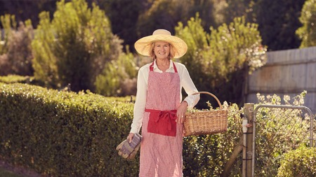 urban gardening: Smiling senior woman standing at her garden gate holding a basket and gardening gloves, while wearing a straw hat and apron, ready for some backyard urban farming