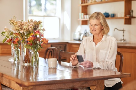 one senior adult woman: Senior woman sitting at a wooden table in her tidy rustic kitchen, reading a text message on the screen of her mobile phone, while having a mid-morning cup of coffee