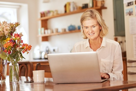 senior adults: Positive senior woman smiling while typing on her laptop, while sitting at a rustic wooden table in a bright kitchen