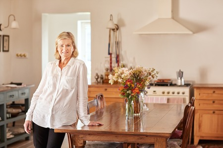 clean home: Portrait of a confident senior woman at home, leaning casually on a wooden table in her clean and tidy kitchen, which has relaxed rustic style to it