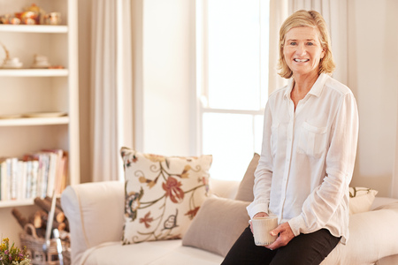 homeware: Portrait of a senior woman smiling confidently and sitting casually on the arm of her couch in her neat and tidy living room at home Stock Photo