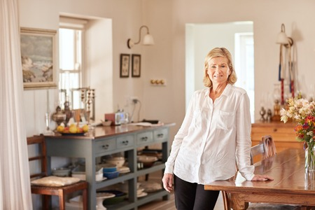 homeware: Potrait of a relaxed senior woman in a tidy kitchen with lots of light and a rustic style, leaning casually on a wooden table with flowers