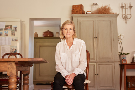 inside house: Portrait of a senior woman with modern dress sense, sitting and looking honestly at the camera in her home which has a gentle rustic style