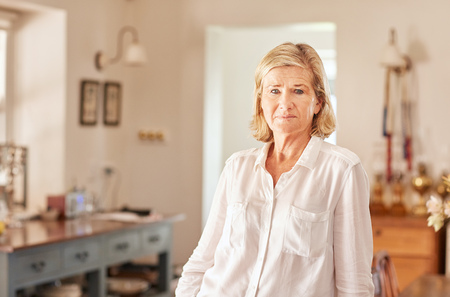 senior female: Candid portrait of a senior woman looking at the camera with an expression of seriousness, while standing in a rustic room with beautiful light Stock Photo