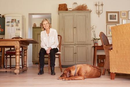silla de madera: Bajo el ángulo retrato de cuerpo entero de una mujer mayor que sonríe con confianza mientras está sentado en una silla de madera en su casa de estilo rústico, con su fiel perro mascota tendido en el suelo cerca de sus pies