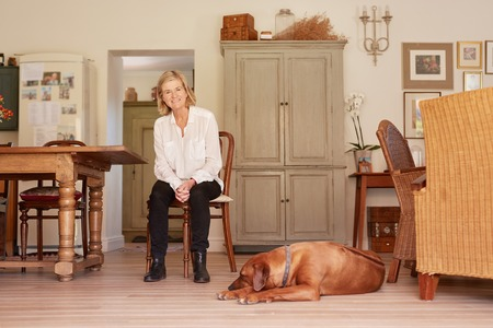 woman sitting on chair: Low angle full length portrait of a senior woman smiling confidently while sitting in a wooden chair in her rustic style home, with her faithful pet dog lying on the floor near her feet Stock Photo