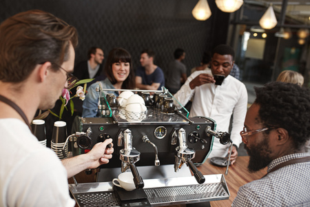 espresso machine: Barista being trained to use an espresso machine in a busy modern coffee shop, with customers of mixed races drinking coffee at the counter