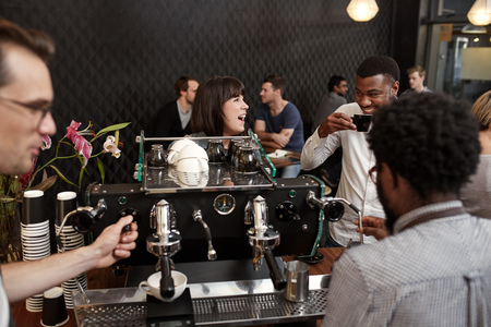 Young woman laughing out loud while standing at the counter of a busy coffee shop, with her African guy friend, while baristas are making cappucinos at the coffee machine