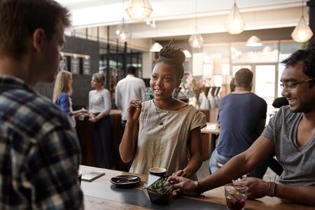 Mujer africana empresarial sonriendo y gesticulando durante una reunión en una cafetería moderna ocupada con dos hombres Foto de archivo - 54727201