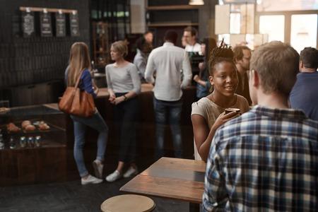 美しいアフリカの女性は彼女の後ろにカウンターに立っている他のお客様で忙しいコーヒー ショップで友人と話して