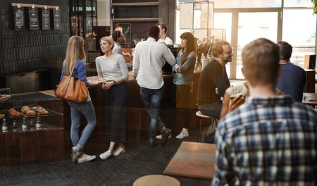 Bekijk via een raam van een trendy moderne koffiehuis met sommige klanten staan ??praten op de houten toonbank, en andere klanten zitten aan tafels Stockfoto - 54727204