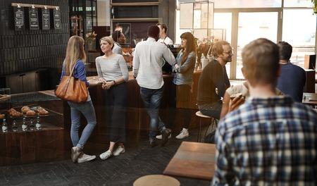personas dialogando: Ver a través de una ventana de una tienda de café moderno de moda con algunos clientes de pie hablando en el mostrador de madera, y otros clientes sentados en las mesas