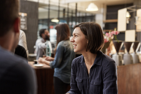 bobbed: Candid shot of a woman with bobbed brunette hair looking away at someone out of frame and smiling broadly and with confidence, while customers are being served in the background Stock Photo