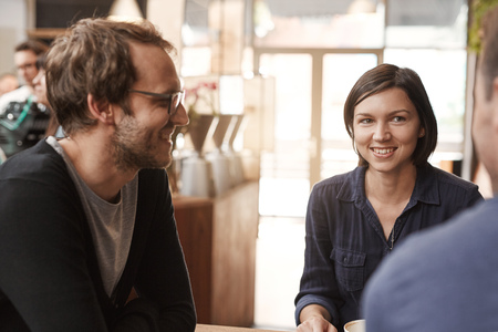 confidently: Young woman sitting in a modern cafe with male friends smiling confidently while on lunch break from work