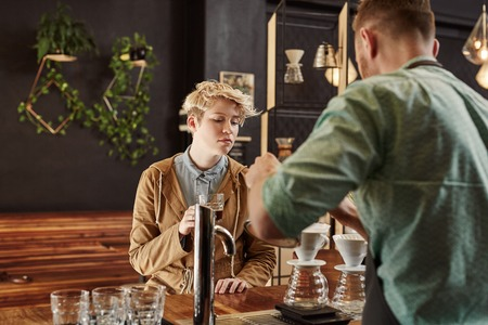 coffees: Woman customer watching carefully as a professional barista explains how the modern coffee shop where he works makes such high quality filter coffees Stock Photo
