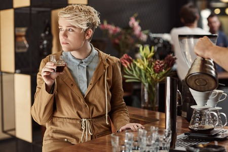 lost in thought: Young blonde woman looking away lost in thought in a trendy modern cafe, while holding a fresh cup of coffee and daydreaming Stock Photo