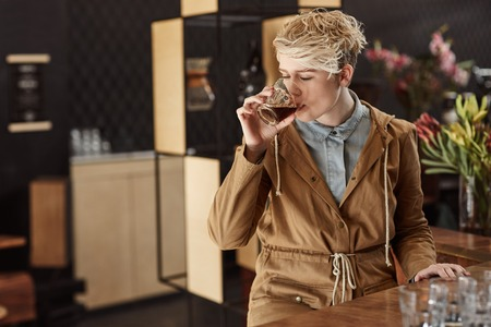 sip: Modern cafe with a young blonde woman in trendy winter clothing taking a sip of fresh coffee with soft morning light falling on her Stock Photo