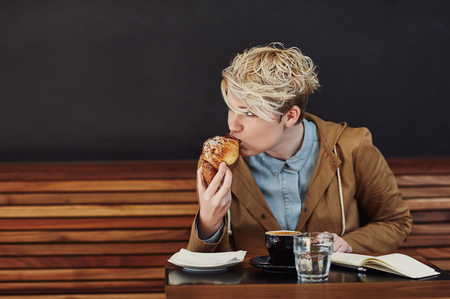 Young woman with trendy blonde hair looking away while taking a bite from her pastry, at a table in a modern cafe with a dark grey wall Banque d'images