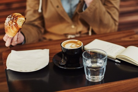 strategizing: Cropped image of a person sitting at a modern cafe holding the croissant they are eating, with an open notebook, cappucino and a glass of water on the table