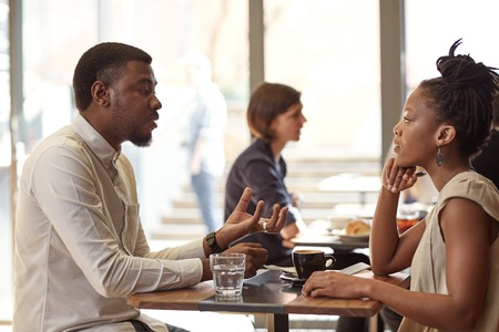 Handsome African businessman discussing his entrepreneurial idea with a respected African businesswoman in a busy and modern cafe Reklamní fotografie