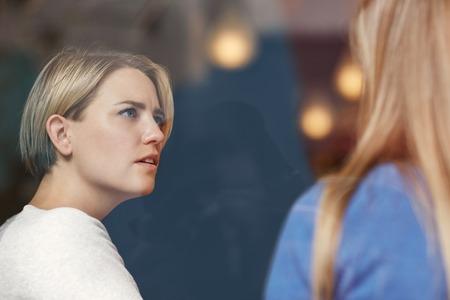 Mujer vista a través de un cristal listineing cuidadosamente con una expresión preocupada en su rostro cuando un amigo está hablando con su