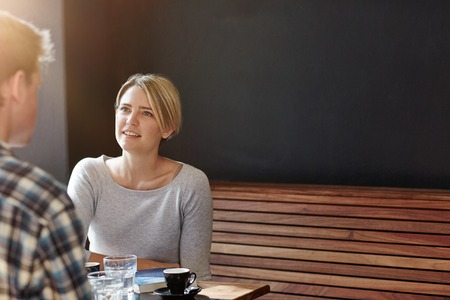 informal: Young blonde woman with short bobbed hair sitting in a modern cafe on a wooden bench with a dark grey wall behind her, having coffee with a male companion Stock Photo