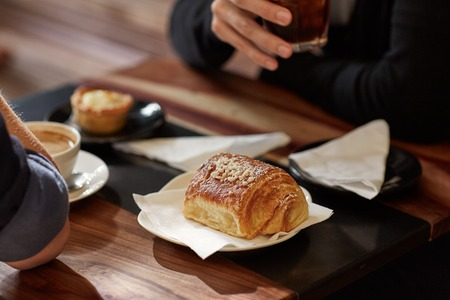 lunch table: Cropped image of two people sitting across from each other at a table in a modern cafe with coffee and croissant on a lunch break