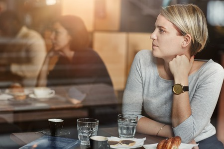 Young blonde woman with trendy short hair having coffee in a modern cafe, sitting at a high table and looking away with her arm up and a modern timepiece visible, as seen through glass Stock Photo