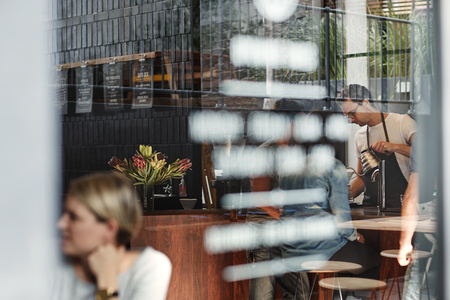 ガラス窓や外側の反射に書く作業、カウンターの後ろのテーブルで顧客バリスタを見ることができますコーヒー ショップのフロント ウィンドウのシ