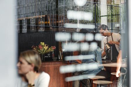 Shot van de voorruit van een coffeeshop, waardoor kunt u de barista werken achter de toonbank, klanten aan tafels, het schrijven op de ruit, en reflecties van de buitenkant