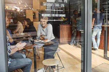 Joven mujer sentada en una mesa alta en un concurrido café moderno, sonriente, mientras disfruta de un café con frineds en una pausa para el almuerzo