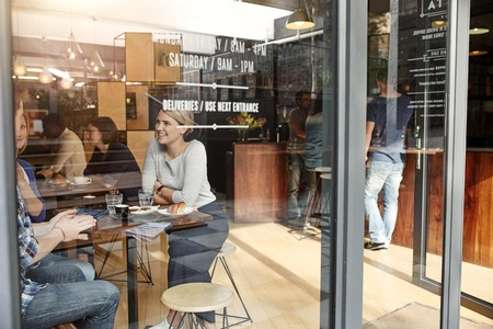 Woman enjoying a coffee break with friends in a busy cafe, smiling and chatting, seen through the glass pane of the front window next to the entrance