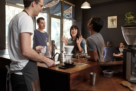 Young woman talking with colleagues and gesturing with her hands, while they are waiting at the counter of a trendy modern coffee shop for their order to be made by the barista