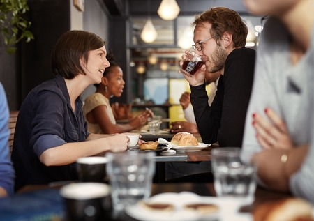 women coffee: Busy cafe with a young couple on a coffee date at a table among other customers, with the woman talking as her boyfriend sips his coffee Stock Photo