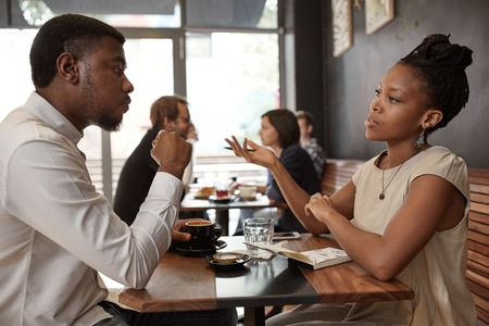 African businesswoman and businessman sitting at a small table in a busy modern cafe, discussing ideas over coffee Stock Photo