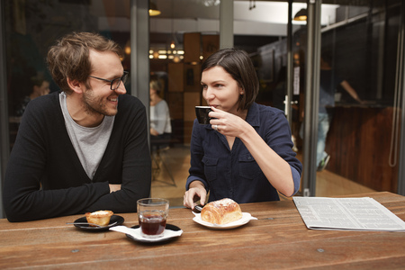 casual men: Young couple sitting at an outdoor table of a modern cafe, the boyfriend smiling at his girlfriend as she is taking a sip of her coffee