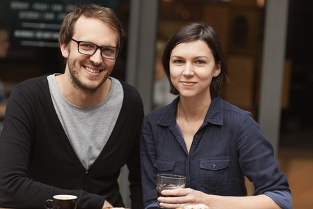 Portrait of a young couple sitting outside and enjoying coffee at a modern cafe, smiling at the camera Stock Photo
