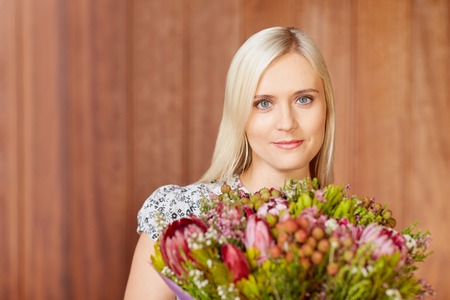 appreciating: Portrait of a beautiful young woman holding flowers Stock Photo