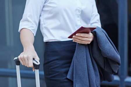 cropped shot: Cropped shot of a businesswoman with luggage and her passport