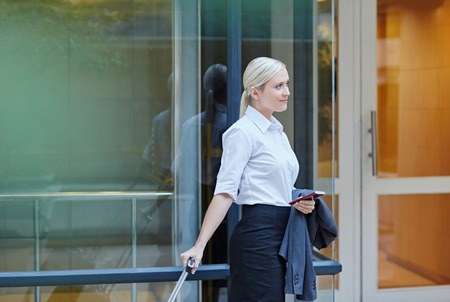 business woman: A young businesswoman walking with travel luggage